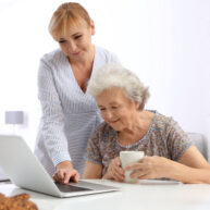 Senior woman and caregiver with laptop at home